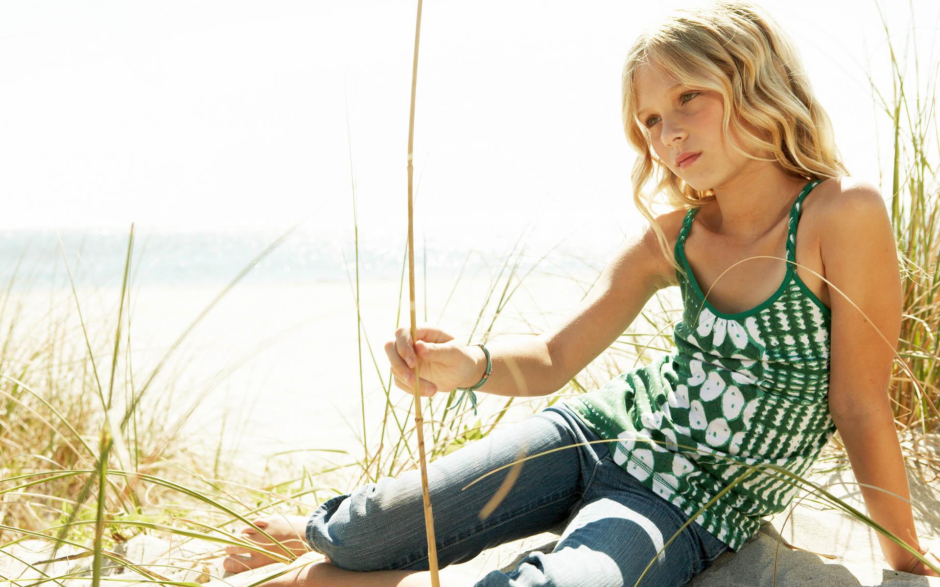 Играющаяся девочка на песке.